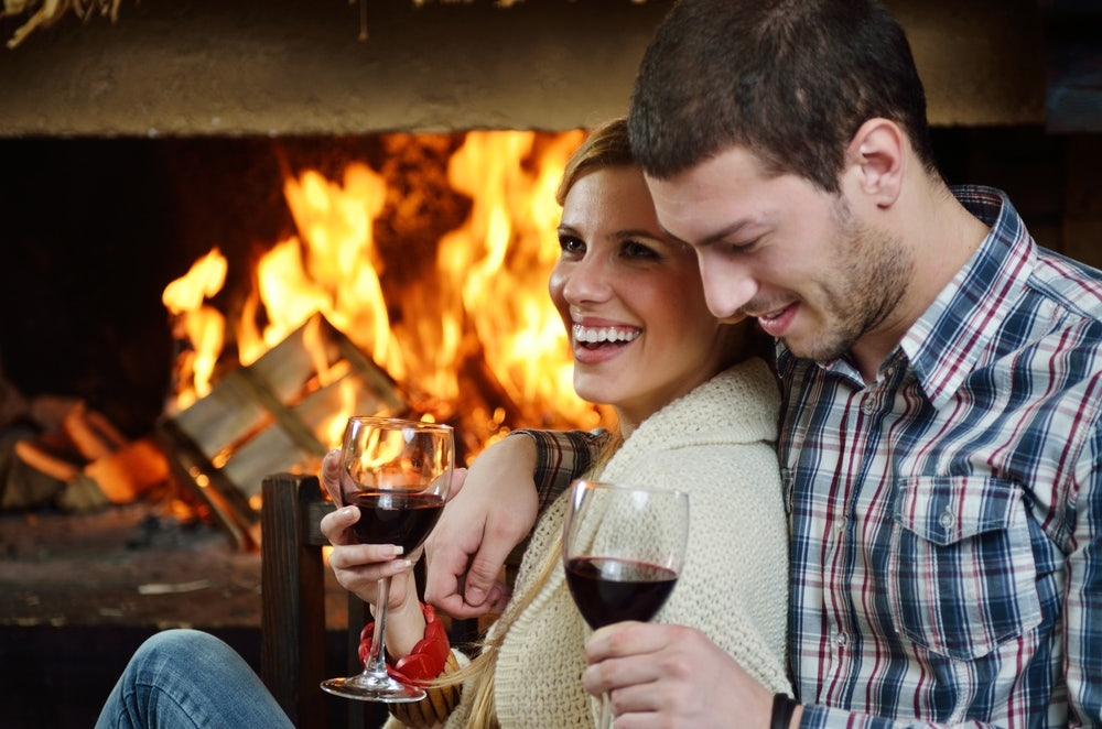 Happy-couple-drinking-wine-by-the-fireplace-in-their-Gatlinburg-condo.jpg
